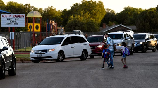 Cars line up at Austin Elementary School on Wednesday for the start of the first day of school.