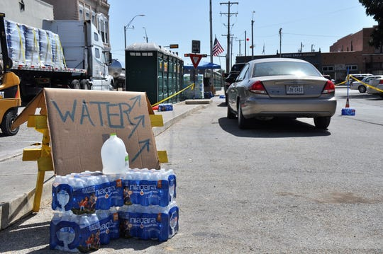 Vehicles wait in line at the water station on the Comanche County Courthouse square Wednesday. Residents could pick up bottled water, fill up water jugs for toilets and use portable toilets at the water station.