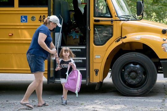 Leslie Hussueng helps her daughter Lexie, 5, off of the school bus as she arrives home from Black Mountain Primary School on Aug. 21, 2019. Hussueng drives her daughter to school in the mornings because the kindergartener would be picked up before 6 a.m. for an 8 a.m. school start time.