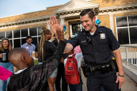 Officer Brice Kerschen greet students on the first day of school at Fremont International Academy on Wednesday, Aug. 21, 2019 in Battle Creek Mich. The Fremont school building closed in 2016 and is reopening its doors as a magnet school where students will learn a second language.