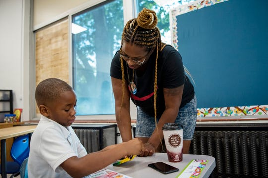 Amina Austin brings her son Amir McFadden to his first day of second grade at Fremont International Academy on Wednesday, Aug. 21, 2019 in Battle Creek Mich. The Fremont school building closed in 2016 and is reopening its doors as a magnet school where students will learn a second language.