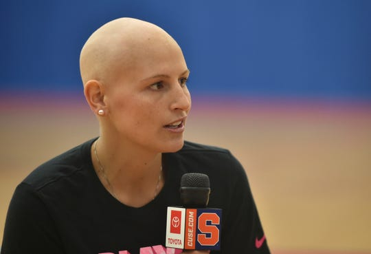 Syracuse University women's basketball guard Tiana Mangakahia holds the microphone as she addresses the media with a shaved head halfway through treatment for breast cancer at the Carmelo K. Anthony Center at Syracuse University in Syracuse, N.Y., Tuesday Aug. 20, 2019. One of the top women's basketball players in the country and a player who nearly elected to enter the WNBA draft, the star from Australia says feedback from doctors has been good and she'll receive more tests Friday updating the status of her recovery. (Scott Schild/The Post-Standard via AP)