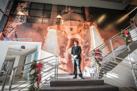 Freelance photographer John Kraus at United Launch Alliance's headquarters in Centennial, Colorado. Behind Kraus is the photo he took of ULA's Delta IV rocket back in March 2017.