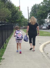 Kim Lynn, left, escorts her daughter, first-grader Abby Lynn, 6, to Bucyrus Elementary School on Wednesday for the first day of school.