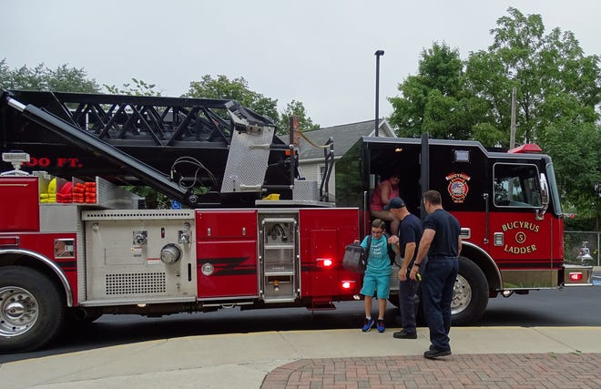 Jeremy Fry arrives at Bucyrus Elementary School for the first day of school on Wednesday, climbing off the Bucyrus Fire Department's No. 5 ladder truck. Jeremy won the ride in a Bratwurst Festival raffle.