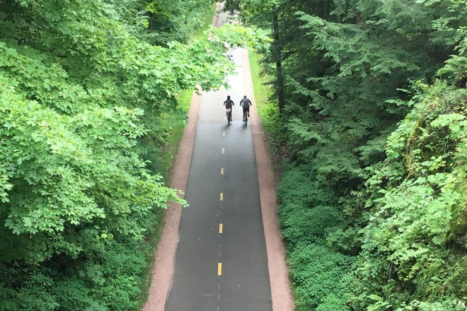 A pair of cyclists pedal south on the Burlington bike path, as viewed from the Rock Point bridge on Aug. 18, 2019.