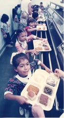 Kindergartener Amanda Buenrostro goes through the lunch line at Menger Elementary School on the first day of school in September 1988.