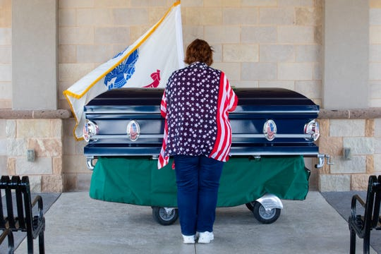 A women pays her respects to Army Pfc. William Conely Carroll Jr. during his funeral at the Coastal Bend Texas State Veterans Cemetery on Wednesday, Aug. 21, 2019.