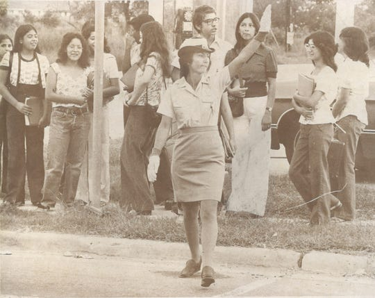 A crossing guard stops traffic as students wait to cross the street on the first day of school in Corpus Christi in August 1975.