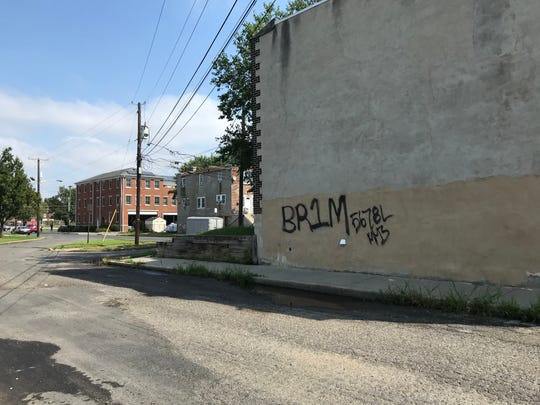 Graffiti tags on the wall of a building in Fairview mark the presence of gangs in the neighborhood.