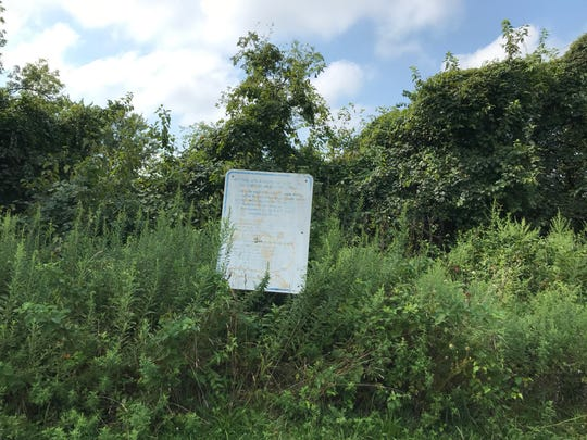 An old sign marks where renovations to the park behind Malandra Hall in Fairview once took place. Now the area around the community center has overgrown vegetation and, some residents say, has become a haven for drug users.