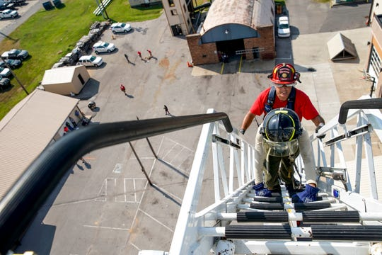 A Clarksville firefighter walks up with a recruit to the top of an engine's ladder during the CFD's agility testing course at Clarksville Fire Rescue downtown in Clarksville, Tenn., on Tuesday, Aug. 20, 2019.