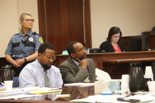Reginald Nesmith looks down while sitting with his attorney in a Montgomery County courtroom on Aug. 21, 2019, where he was facing charges in the 2013 shooting death of Daniel Reed.
