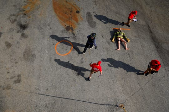 Instructors walk over to a dummy to be carried across the parking lot by CFD recruits during the CFD's agility testing course at Clarksville Fire Rescue downtown in Clarksville, Tenn., on Tuesday, Aug. 20, 2019.