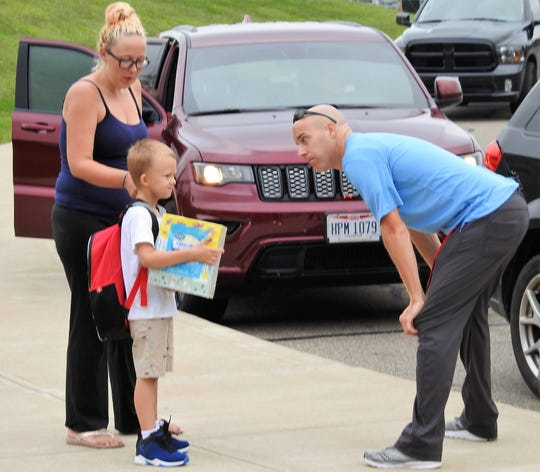 Mystic Carroll and first-grader Osin Addy are greeted by physical education teacher Jamie Duling on the first day of school at Coshocton Elementary School.