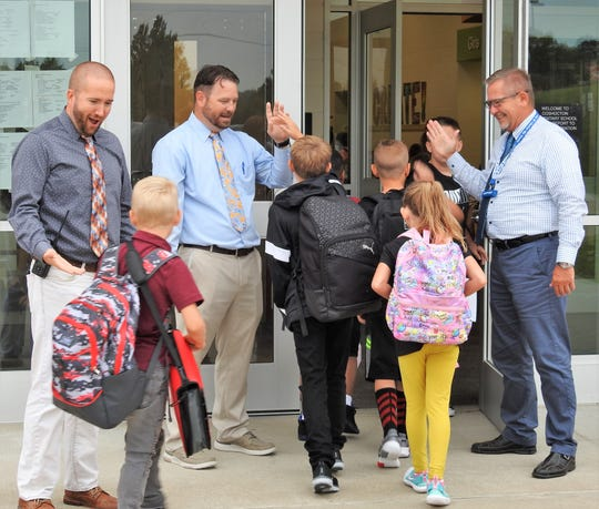 Instructional Technology Director Jason Olinger and assistant principals Tony Meiser and John Casey greet students as they enter Coshocton Elementary School on Wednesday for the first day of school.
