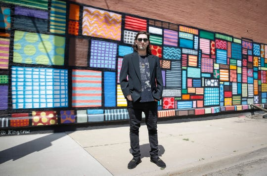 Des Moines artist Chris Williams poses for a photo in front of a mural he painted at Sixth and College avenues in Des Moines. The mural was featured in a Hy-Vee commercial that aired during the Super Bowl. Williams is suing the grocery chain for copyright infringement.