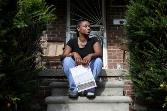 Mechelle Burrell, 36 on the front steps of her Detroit home on Tuesday, August, 20, 2019 holding the legal document that was taped to the front door of the home.