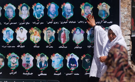 An Afghan woman cries as she touches a banner displaying photographs of victims of the Dubai City wedding hall bombing during a memorial service in Kabul, Afghanistan, Tuesday, Aug. 20, 2019.
