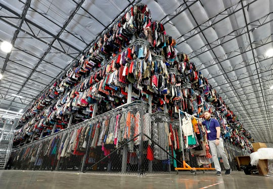FILE - In this March 12, 2019, file photo thousands of garments are stored on a three-tiered conveyor system at the ThredUp sorting facility in Phoenix. J.C. Penney and Macy's are in the midst of rolling out a few dozen ThredUp branded shops each in time for the back-to-school shopping season. The partnerships follow a similar deal with department store retailer Stage Stores.