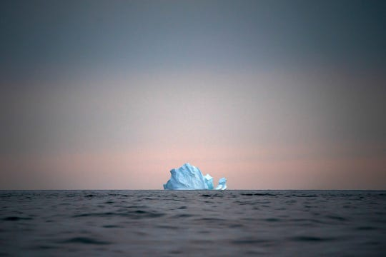 In this Aug. 15, 2019, photo, a large Iceberg floats away as the sun sets near Kulusuk, Greenland. Greenland is where Earth's refrigerator door is left open, where glaciers dwindle and seas begin to rise. Scientists are hard at work there, trying to understand the alarmingly rapid melting of the ice. For Greenland is where the planet's future is being written.
