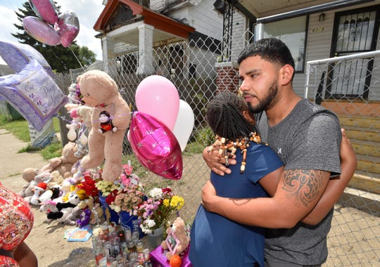 Francisco Hernandez, uncle of nine-year-old Emma Hernandez, who was mauled to death by three dogs in her southwest Detroit neighborhood Monday, receives a hug from Tira Nowden, 9, next to a memorial in front of Emma's house.