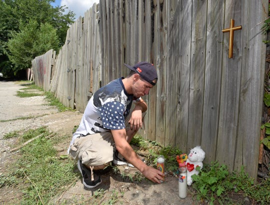 Edward Cruz visits a makeshift memorial in the alley near the spot where nine-year-old Emma Hernandez was mauled to death by three pit bulls, Monday, near her home.
