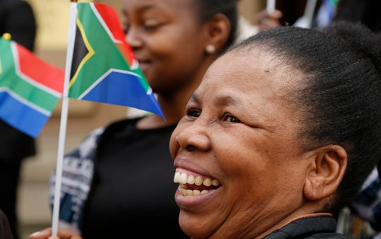 Women hold miniature South African flags as Nelson Mandela Foundation's CEO, Sello Hatang, speaks to the press on the steps of the Johannesburg High Court, Wednesday, August 21, 2019.