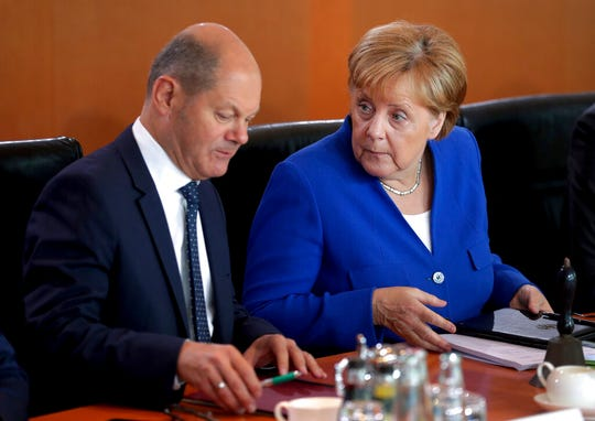 German Chancellor Angela Merkel, right, and German Finance Minister Olaf Scholz, left, talk as they arrive for the weekly cabinet meeting at the Chancellery in Berlin, Germany, Wednesday, Aug. 21, 2019.