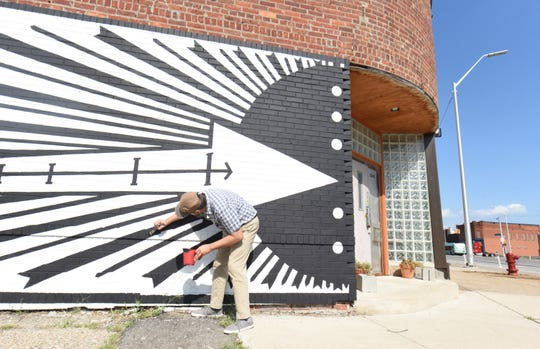 Standfest touches up his Holding House mural in Detroit, which echoes the graphic style of the Italian Futurists.