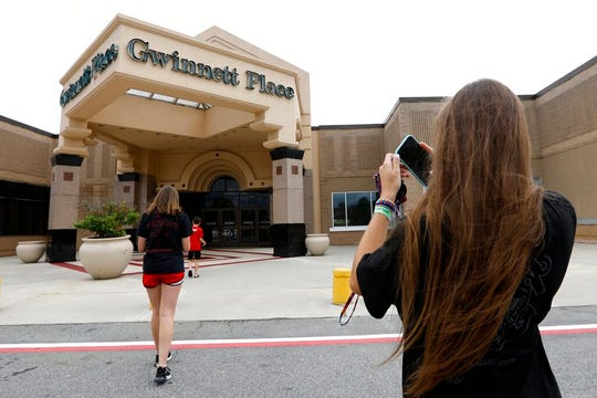 Brinley Rawson, a 17-year-old Stranger Things fan from Gwinnett County, snaps a photo of Gwinnett Place Mall in Duluth, Ga. Stranger Things filmed much of season three at the mall, which was called Starcourt Mall in the show.
