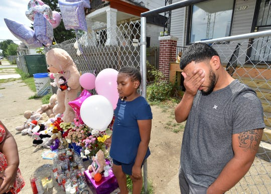 Francisco Hernandez, uncle of nine-year-old dog-mauling victim Emma Hernandez grieves the tragic loss of his niece as he stands with Tira Nowden, 9, of Detroit beside a makeshift memorial in front of Emma's house.