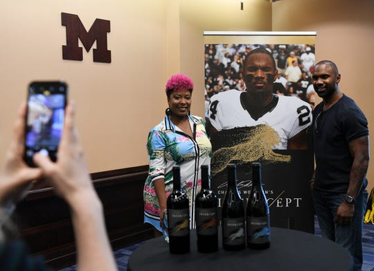"A.J. Williams of Detroit has her photo taken with former Michigan football star Charles Woodson as  Woodson's wine, Woodson's ""Intercept,"" is introduced at the Junge Family Champion's Center in Ann Arbor."