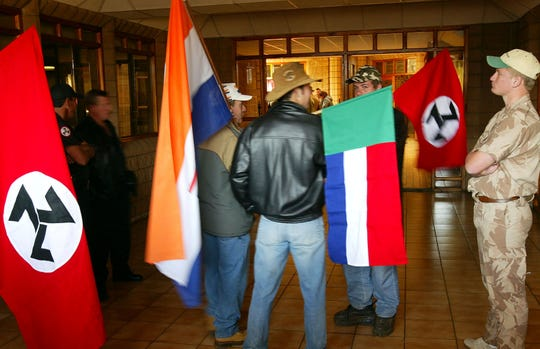 "In this June 11 2004, file photo, supporters of the Afrikaner Resistance Movement (AWB) display an old South African flag, second from left, an old Afrikaner ""Vierkleur"" flag and swastika-like flags as they await the release of their leader, Eugene Terre'Blanche from prison in Potchefstroom, South Africa."