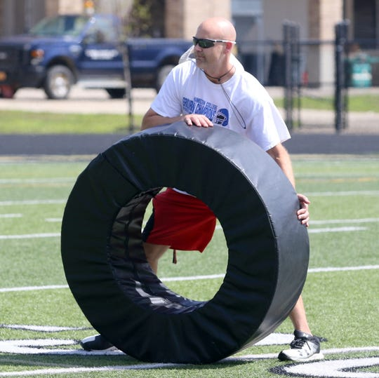 Corning assistant coach Tim Hughes leads a drill during varsity football  practice Aug. 21, 2019 at Corning Memorial Stadium.