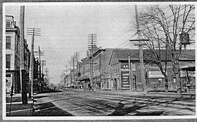 Front & Birchard, 1890s.   This early photo looks north on Front Street across Birchard toward the large livery building on the NE corner that was the former Hafford Carriage Works, later replaced by Bierly's Sunoco and now Grund Drug.  The buggies and utility poles date the picture to the 1890s.  Behind the livery building, the massive Jackson underwear factory that extended all the way to Garrison Street.  At the far right is the porch of a house where the Paramount Theater now stands.