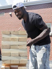 St. John's shelter resident Shantwan Brown plans his next move at giant Jenga during a cookout Aug. 15, 2019, at the Micah Center in Green Bay, Wis.