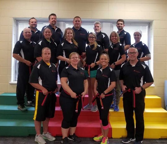 Teachers and law enforcement members from Kewaunee and Door counties show off their belts after graduating from the COREMatters Project training to teach resiliency to local middle school students.