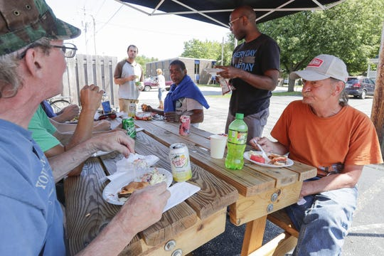 St. John's shelter residents socialize during a cookout Aug. 15, 2019, at the Micah Center in Green Bay, Wis.