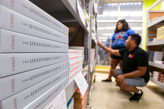 Political science student Joseph Madlangbayan and secondary education/English student Jamie Howard, standing, shop for recommended textbooks at the University of Guam bookstore in Mangilao on Wednesday, Aug. 21, 2019.