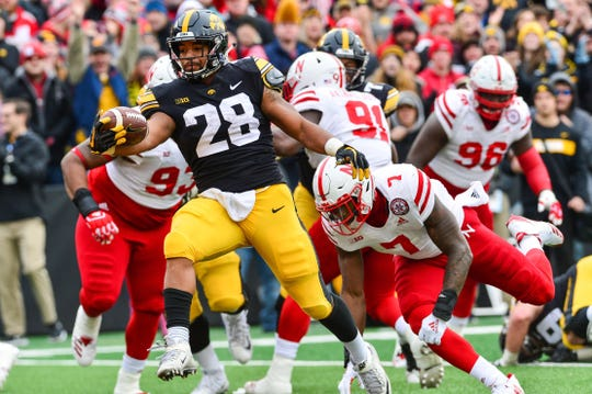 When Iowa and Toren Young (left, outrunning Nebraska's Mohamed Barry) can defeat the Cornhuskers on Nov. 29 will decide the Big Ten West title.