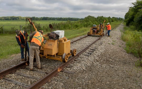 A crew for Utah's A & K Railroad Materials removes railroad spikes Wednesday on the Nickel Plate Line.