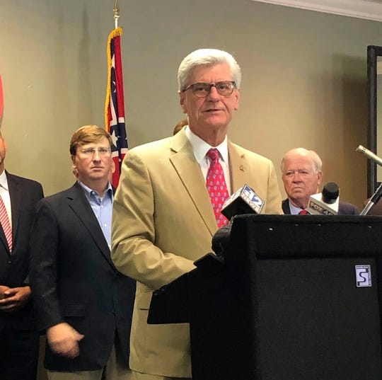Mississippi Gov. Phil Bryant, center, says Tuesday, Aug. 20, 2019, at the state Republican Party headquarters in Jackson, Miss., that he is supporting Lt Gov. Tate Reeves, left, in the Aug. 27 runoff that decides the GOP nominee for governor. Bryant is term-limited and could not run again. Republican former Gov. Haley Barbour, right, also says he is supporting Reeves over retired Mississippi Supreme Court Chief Justice Bill Waller Jr.