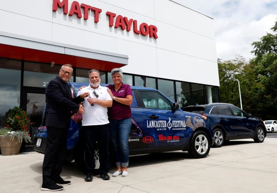 James Cuci, from Orland Park, Ill., stands between James Clark, managing partner of Matt Taylor Kia, and Deb Connell, executive director of the Lancaster Festival, Wednesday, Aug. 21, 2019, at Matt Taylor Kia in Lancaster.