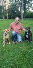 White Lake resident Scott Lorms with his two emotional support animals, dogs named Curiz (left) and Riley (right). Lorms is suing Brighton-based property manager T&R Properties and Zahler Management for denying him the right to apply to rent an apartment in Pinckney because they do not allow dogs but Lorms has a notification from his doctor for them.