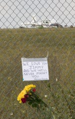 Flowers and a sign of remembrance hang on the fence off Tooley Rd. surrounding the Spencer J. Hardy  Airport Wednesday, Aug. 21, 2019 with the plane that crashed the day before in the background.
