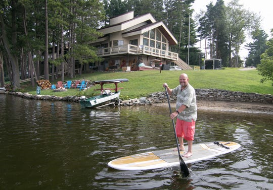 Harold Cole paddleboards Wednesday, Aug. 21, 2019 along the shore of his home designed by Bill Weaver. The home is characterized by mult-tiered roof lines and curves.