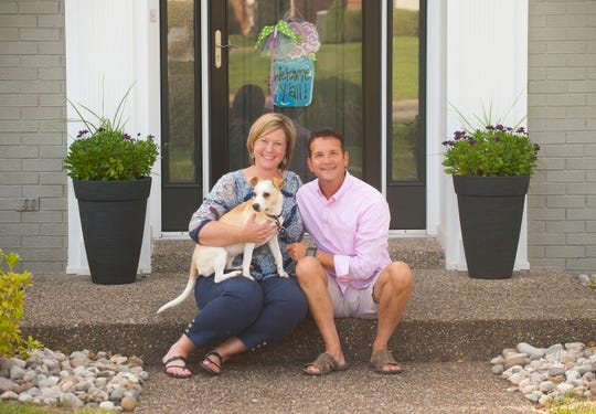 Shannon and Tom Steltenpohl and their one-year-old Jack Russell terrier, Roxy, sit on the front steps of their Douglass Hills  home.