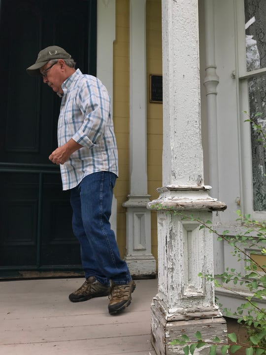 Billy Roback, president of the Perry Historical Society, locks up the front door of the Calkins-MacQueen House in Perry Aug. 20, 2019. The fate of the house is uncertain.