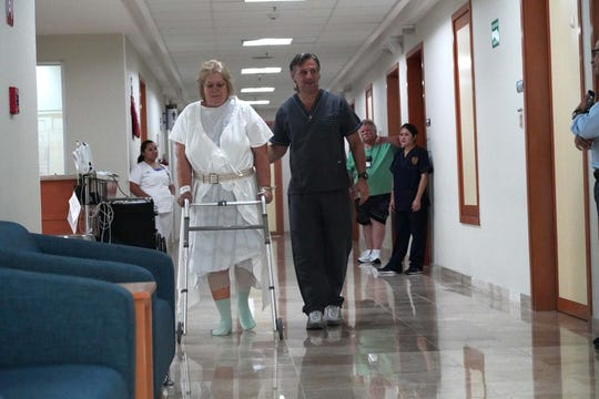 Physical therapist Carlos Bauque helps Donna Ferguson walk as she recuperates from her surgery.